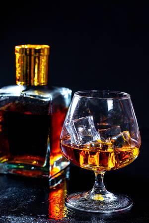 Cognacflasche und mit Likör und Eiswürfeln vorbereitetes Glas vor dunklem Hintergrund