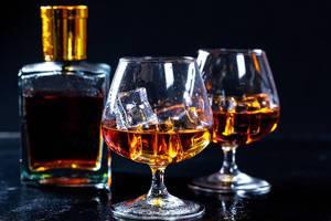 Cognacflasche und zwei Gläser gefüllt mit Likör und Eiswürfeln vor dunklem Hintergrund