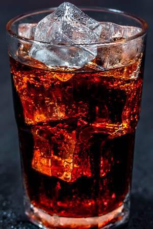 Cola mit Eiswürfeln in einem Glas auf schwarzem Hintergrund