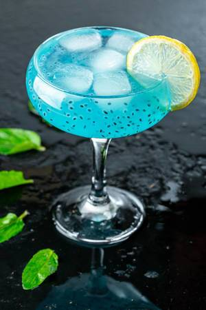 Cold blue cocktail with ice,lemon slice and mint leaves on black background