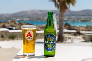 Cold Heineken beer next to a filled glass on a table at a Beach on Paros, with view of the Mediterranean Sean