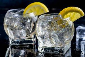 Cold lemonade with ice cubes on black background (Flip 2019)