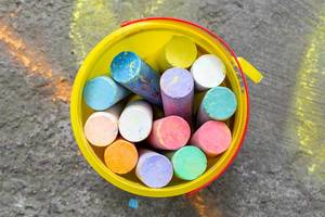 Colored chalk in a yellow bucket. Top view