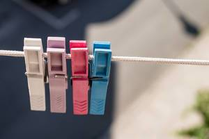 Colored clothes pins on a clothes line rope.