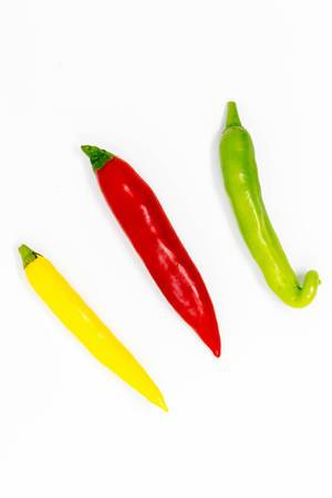 Colorful chilis on white background