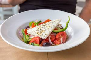 Colorful Greek salad wit feta cheese and fresh vegetables on a white plate