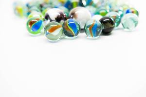 Colorful marbles on a white surface