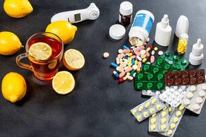 Colorful medicines and pills with a Cup of tea and lemons. Concept folk medicine and traditional medicine (Flip 2019)