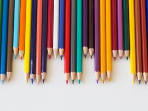 Colorful Pencils laying next to each other on white Background