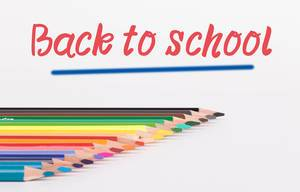 Colorful pencils on white background with text Back to school