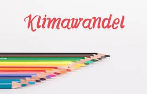 Colorful pencils on white background with text Klimawandel