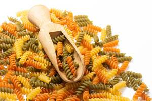 Colorful raw macaroni with wooden spatula on the top