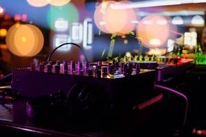 Colourful image of deejay console with bokeh lights before a party