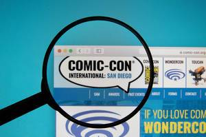 Comic-Con International website on a computer screen with a magnifying glass
