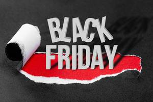 "Conceptual background to Black Friday. Black torn paper and the inscription ""black friday"" on a red background"