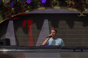 Conro talks to the visitors of Tomorrowland festival with huge visual screen in the background