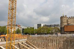 Construction with crane and excavator at Rudolfplatz in Cologne with the medieval city wall in the background