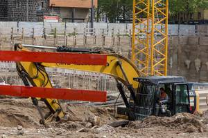 Construction worker sits in a crawler excavator at the construction site at Rudolfplatz in Cologne