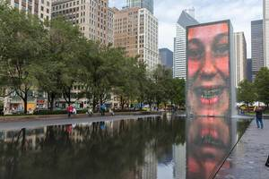 Controversial attraction in Chicago: a human face is reflected on the granite pool of the Crown Fountain at Millennium Park