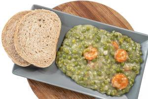 Cooked Green Peas with Carrots served on the plate with bread (Flip 2019)