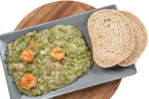 Cooked Green Peas with Carrots served on the plate with bread