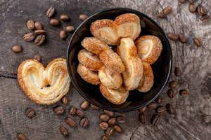 Cookies in a black bowl on a wooden background with coffee beans
