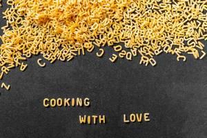 Cooking with Love aus Buchstaben-Pasta auf schwarzem Hintergrund