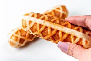 Corn dog in a waffle close-up in a female hand (Flip 2020)