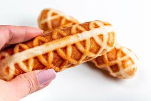 Corn dog in a waffle close-up in a female hand