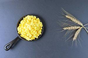 Corn flakes and wheat ear at breakfast, dark background