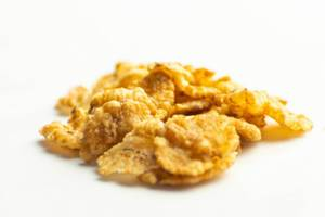 Corn flakes spilled on a white background