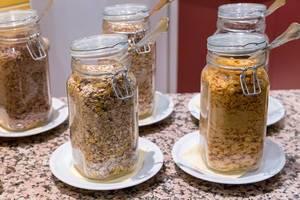 Cornflakes und diverse Müsli-Sorten in Glasbehältern