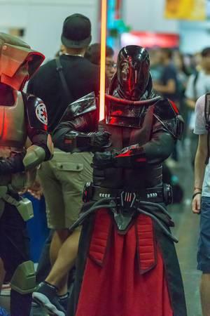 Cosplayer gekleidet als Sith Lord mit rotem Lichtschwert