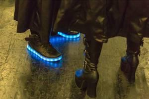 Cosplayer in schwarzes Leder gekleidet mit leuchtenden Schuhen