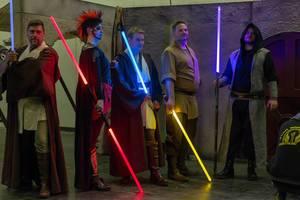 Cosplayer verkleidet als Jedi und Sith mit Lichtschwertern