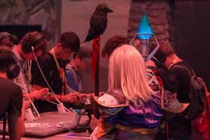Cosplayerin gekleidet als Magierin am Messestand von Torchlight Frontiers