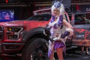 Cosplayerin posiert für Fotos vor einem Geländewagen am Messestand von Trust Gaming
