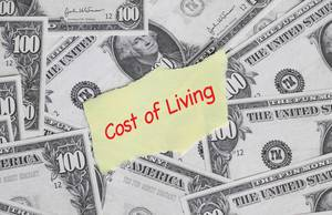Cost of living text with US dollar banknotes