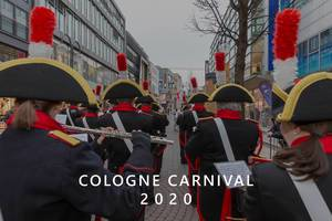 "Costumed Marching band in uniform from behind during carnival Monday with the picture title ""Cologne Carnival 2020"""