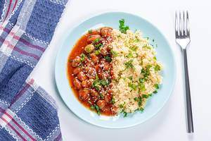 Couscous porridge with beans in tomato sauce, parsley and sesame seeds. Top view