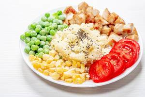 Couscous with Chia seeds, young peas, corn, tomatoes and baked chicken on a white plate (Flip 2019)
