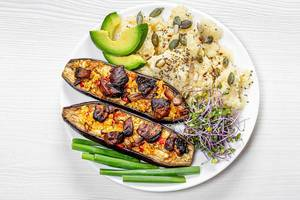 Couscous with seeds, micro greens cabbage, baked eggplant and pieces of fresh avocado and young onions on a plate (Flip 2019)