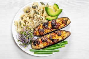 Couscousmix mit Samen, neben Keimsprossen also Superfood, gebackenen Zucchini mit Gemüsefüllung, Avocadoscheiben und Frühlingszwiebeln