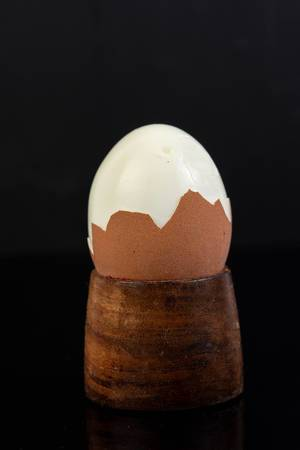 Cracked Boiled Egg above black reflective background