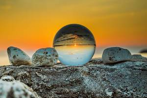 Creative Sunset Photo with flipped Sea Horizon in Lens Ball next to Stones at Golden Hour