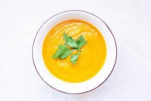 cremige gelbe Karottensuppe mit Petersilie in weißer Suppenschale auf weißem Hintergrund