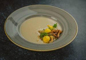 Cremige Pilzsuppe garniert mit Waldpilzen und Kresse auf grauem Keramikteller - Nahaufnahme