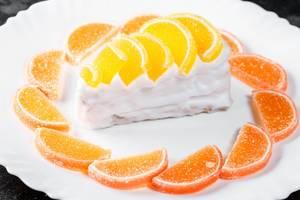 Cremiger Sahne-Kuchen mit Orangen- und Limonenmarmelade als süßer Nachtisch, auf einem weißen Teller