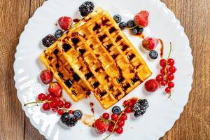 Crispy Belgian waffles with chocolate topping and ripe berries on a white plate. Top view (Flip 2019)