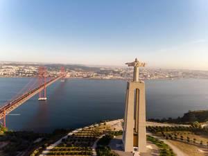 Cristo Rei Statue von hinten mit Ponte 25 de abril Brücke in Almada Lissabon